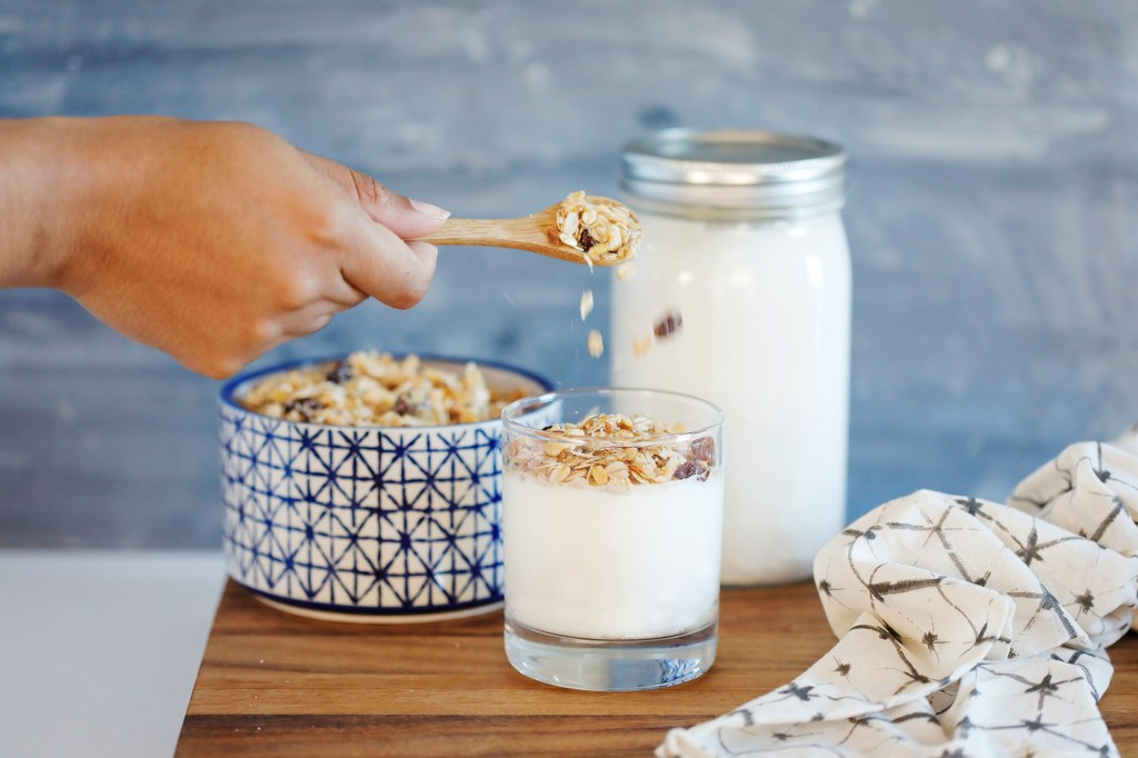 pouring granola onto homemade yogurt