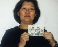 Photograph of an adult Davidine Sim holding a phot of herself as a child
