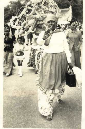 Black and white photo of a woman, not in costume, leading the parade
