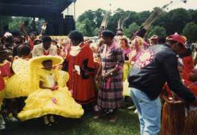 Photograph of two women inspecting a group of youngt girls in bright yellow costumes