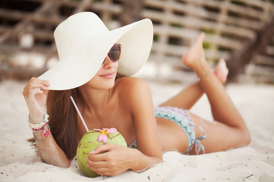 woman wearing a swimsuit and hat on the beach