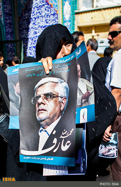 A woman donning the chador holds a poster in support of the most reformist former presidential candidate, Aref.