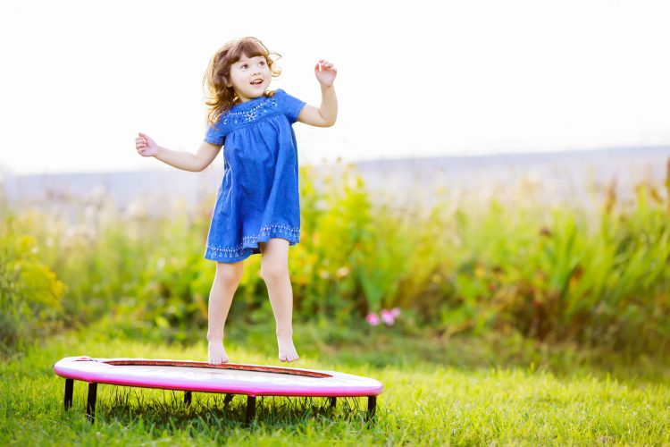 Child jumping on trampoline in a field
