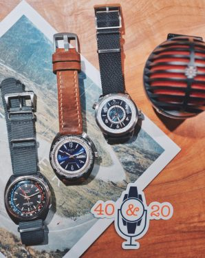 Three different worldtime and gmt watches ontop of a newspaper with a microphone and the 40&20 podcast sticker