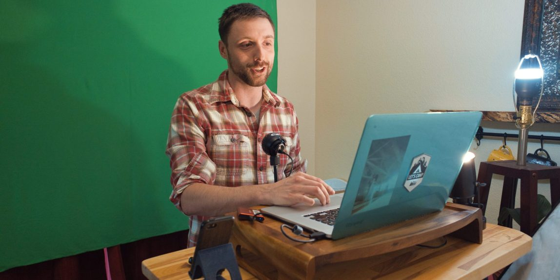 AJ infront of a greenscreen on the curtains of his diningroom with his computer and lights around him in an ad-hoc studio