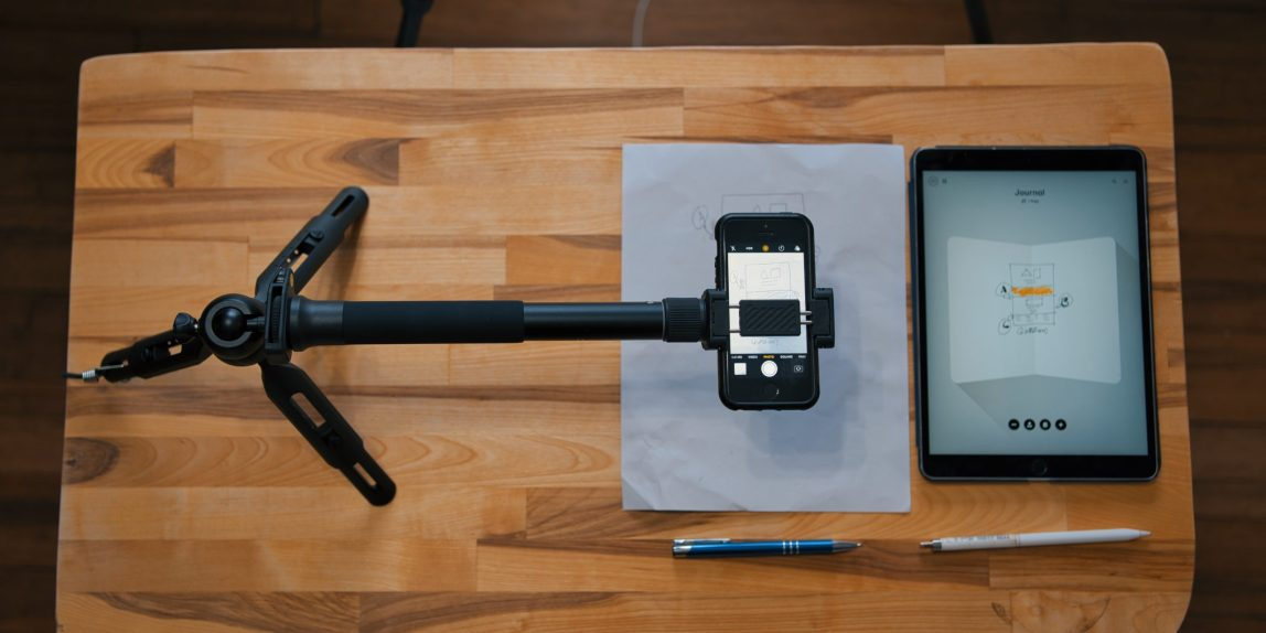 Overhead shot of tripod with extnesion holding an iPhone with the video camera app open, paper and pen below it, iPad pro and pencil beside it