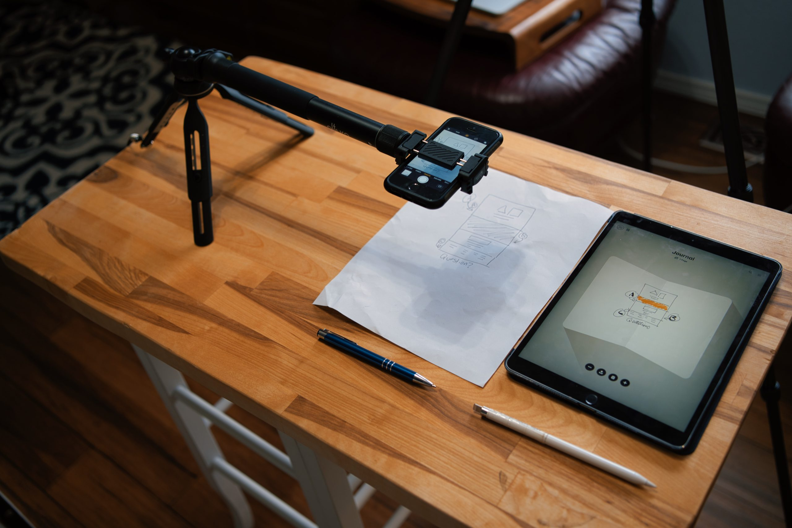 From an angle: Overhead shot of tripod with extnesion holding an iPhone with the video camera app open, paper and pen below it, iPad pro and pencil beside it