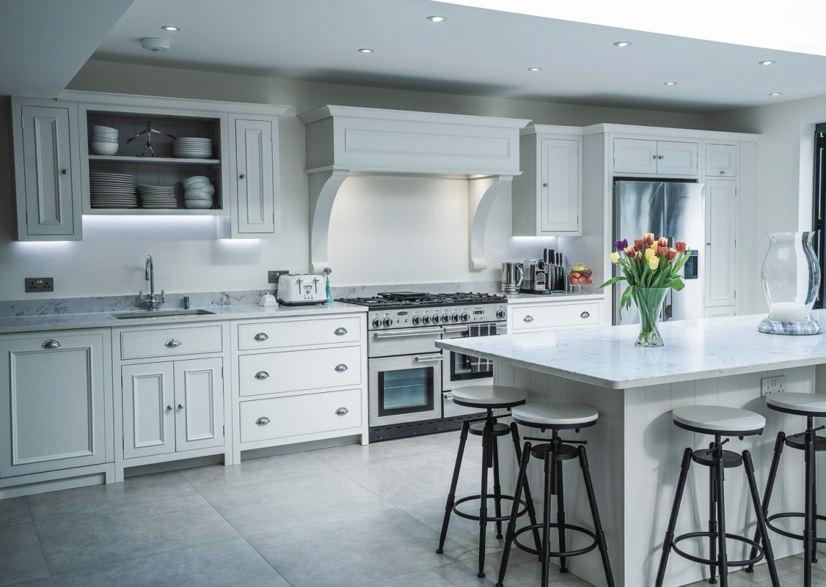A modern white kitchen with flowers on the island. Built by AJ Hammond Builders in Bexhill On Sea, East Sussex