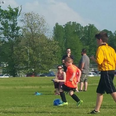 Noah, in the orange with ball, playing soccer