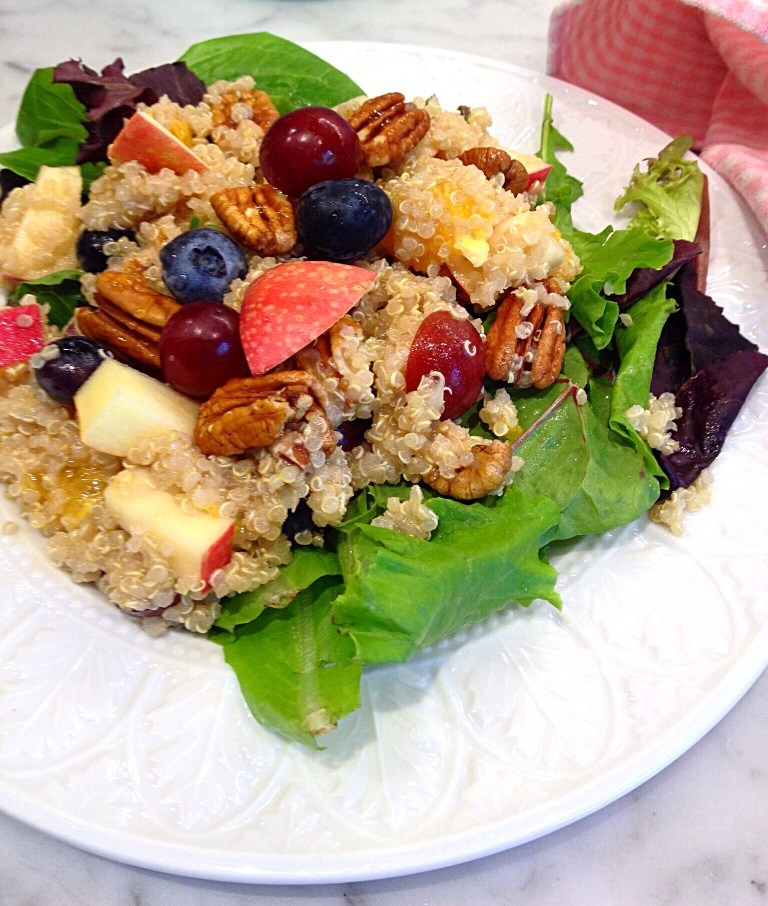 Quinoa Salad with Fruit and Nuts served on a bed of salad greens