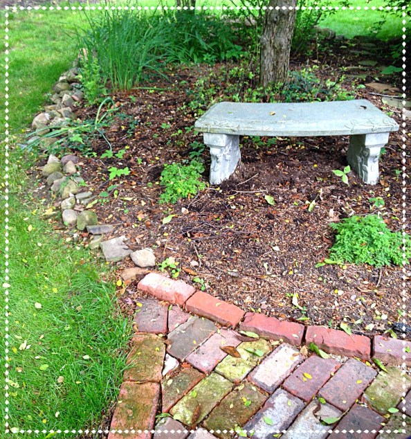 A mulched tree bed is edged with stone and brick