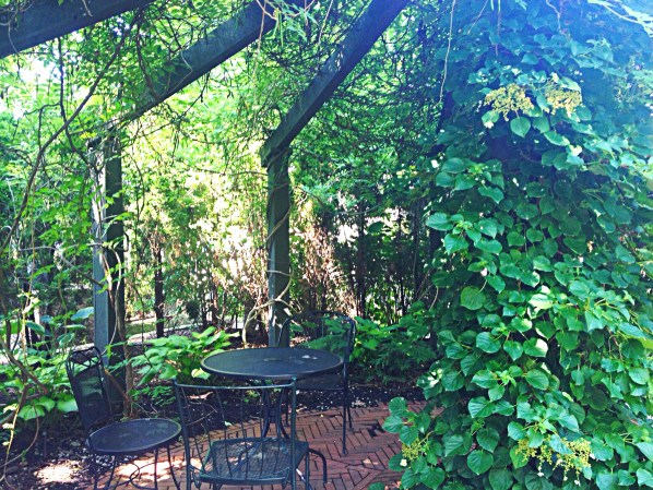 Photo of a spoked arbor frame. The arbor provides leafy shade.