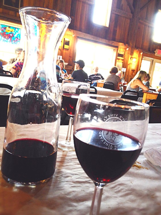 Photo of red wine in liter container and glass