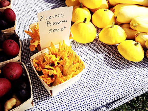 Photo of squash, potatoes, and squash blossoms.