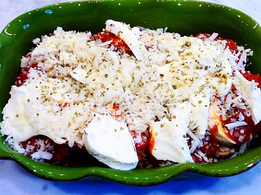 Photo of layered sauce and cheese atop eggplant