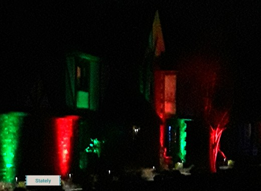 red and green floodlights illuminate the stucco of a Tudor style home