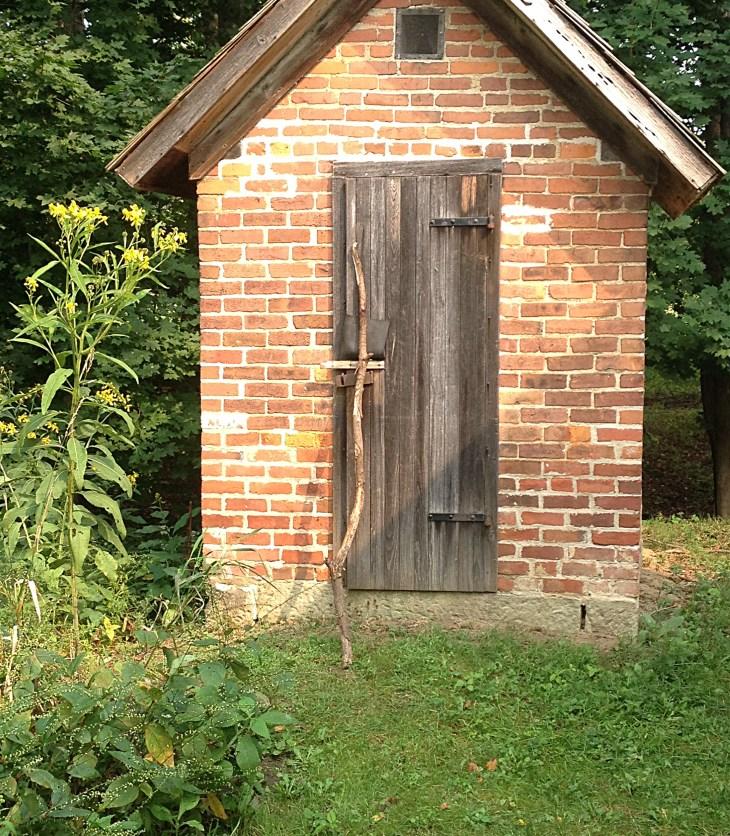 small brick outbuilding behind historic white clapboard farmhouse