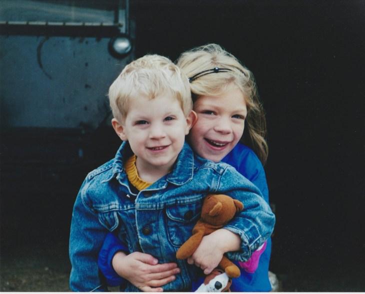 Sister hugs brother and teddy bear and stuffed dog