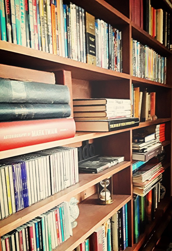 A home library displays shelves of books, CDs, and DVDs