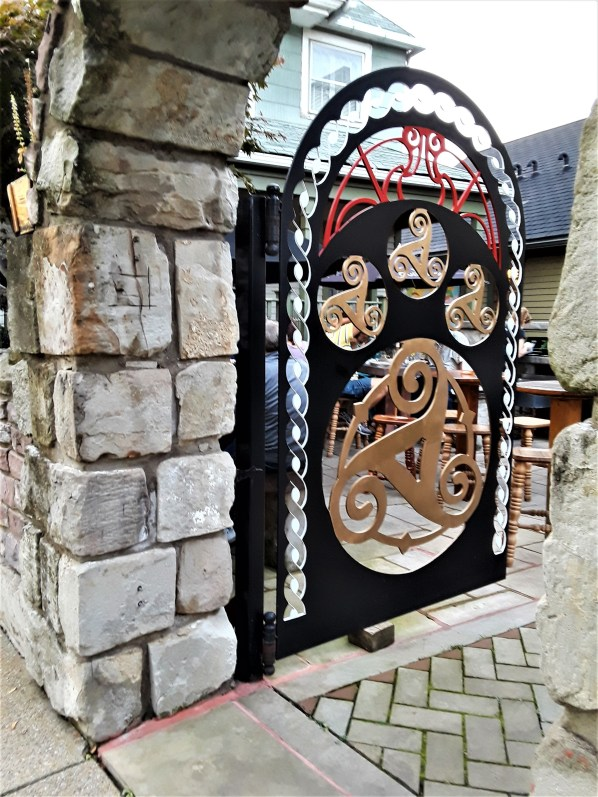 A stylized iron gate welcomes beer lovers to an outdoor patio in the Ohio City neighborhood of Cleveland.