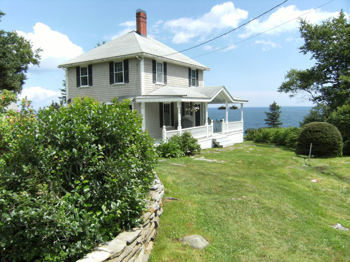 Gray frame cottage with wrap around porch overlooking the Atlantic Ocean.