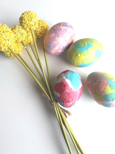 Blown-out eggs are coated with colored bits of tissue paper