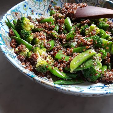 Snap peas and broccoli mixed into cooked red quinoa.