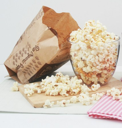 popcorn in a bowl sits next to an empty popcorn bag