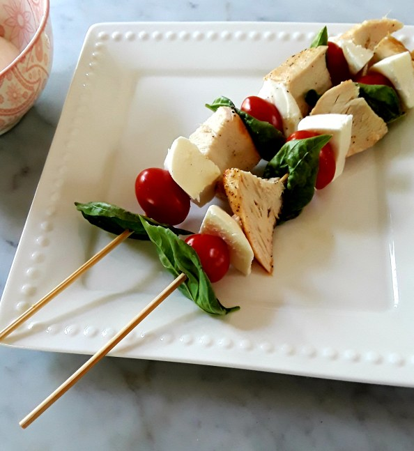 basil leaves, tomato, fresh mozzarella and chicken cubes on a stick
