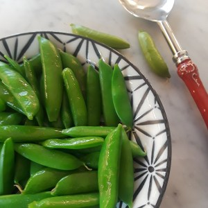 cooked sugar snap peas in a black and white ceramic bowl
