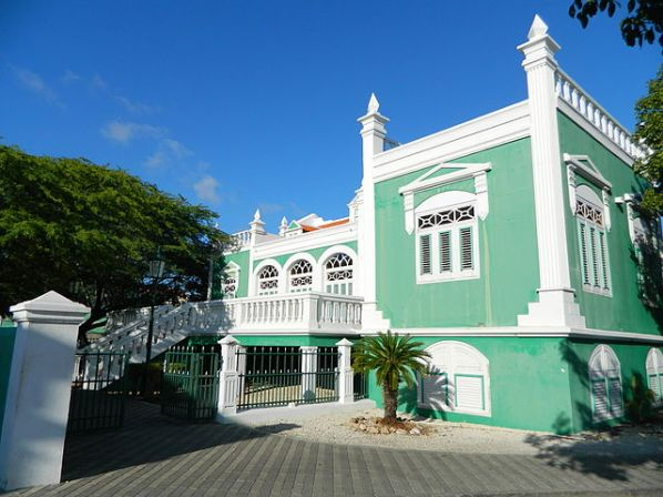 green and white building in downtown Oranjestad