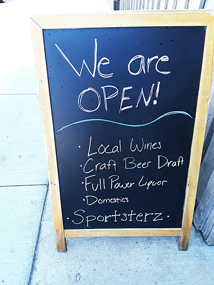 Chalkboard sign advertising local wines, craft beer.