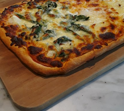 Baked homemade pizza with spinach and cheese toppings