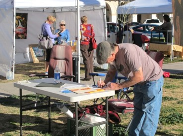 Mike Baker, Artist Festival organizer, sets up the Desert Artist Guild booth.