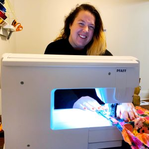 Chelsea sitting at a sewing machine, smiling and sewing a shirt
