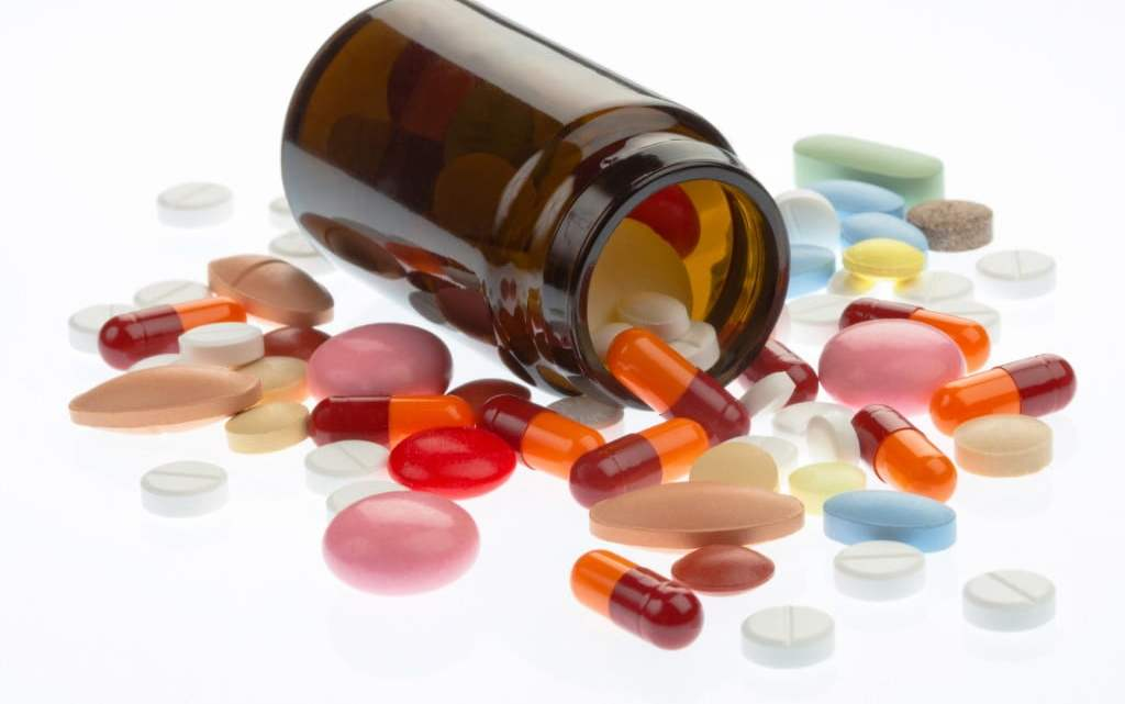 complementary medicines - pills spill out of brown bottle