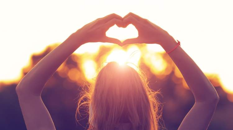 women's heart health: woman makes heart shape with hands backlit by sunset
