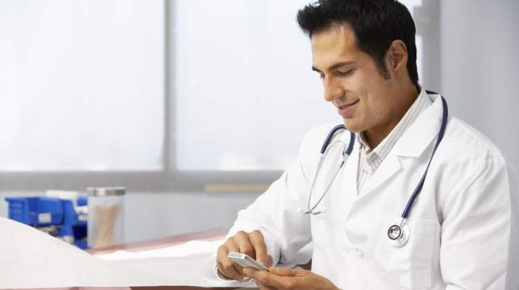 cancer trials app story: male doctor using smartphone