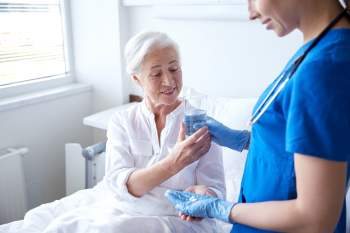 nurse giving medicine to senior elderly older woman at hospital nursing home