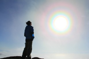 Abe Phyle stands atop Castle Rock, surrounded by an incredible solar corona. © A. Padilla