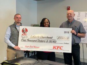 three people holding LaQuita Churchwell's end of year bonus check