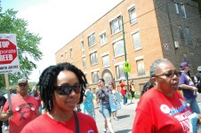 Teachers and CTU supporters march past boarded-up apartments designated for demolition on the southside of Chicago.