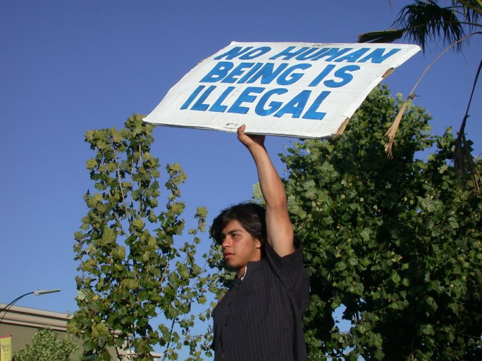 """A man holds a sign reading """"No human being is illegal"""""""