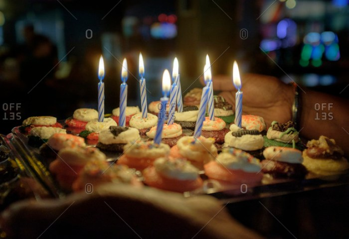 Person Holding Tray Of Cupcakes With Birthday Candles Stock Photo