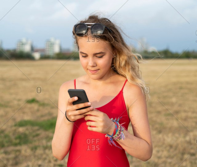 Young Blonde Teenager Checking Cell Phone Outside