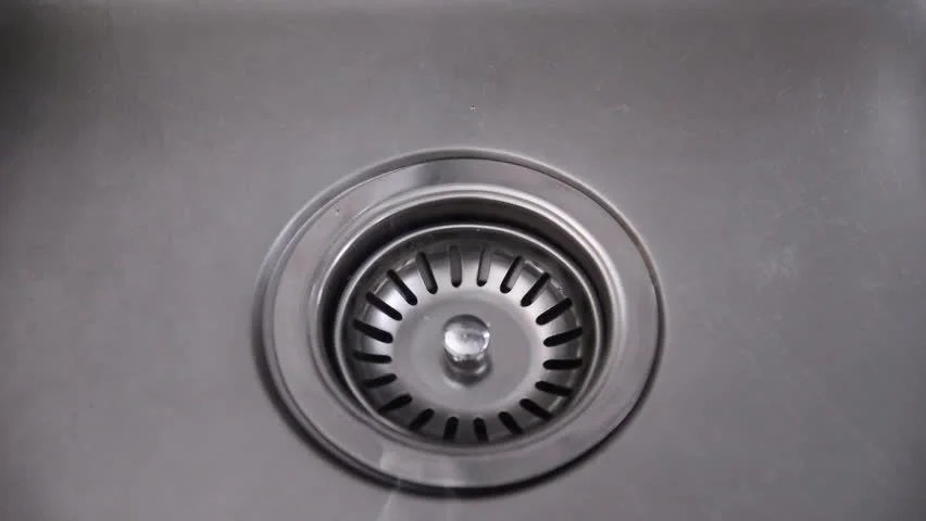 hand removing drain stopper from stock