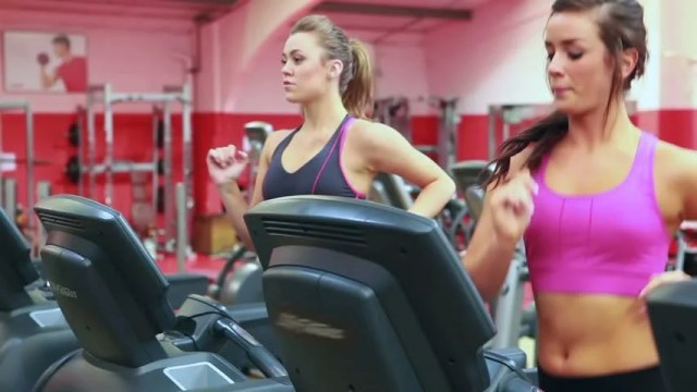 Two Women Running On Treadmills In Gym