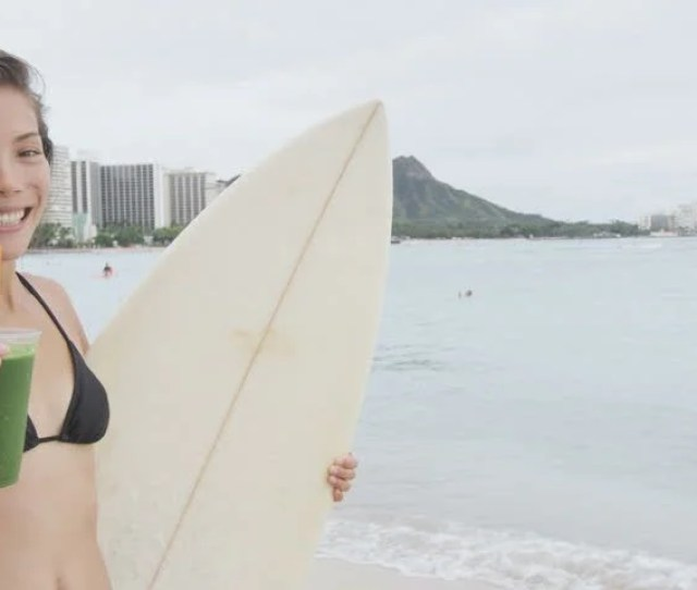 Video Of Sensuous Woman Offering Healthy Drink At Beach She Is Holding Glass And Surf Board Portrait Of Young And Wet Female Is Smiling On Shore