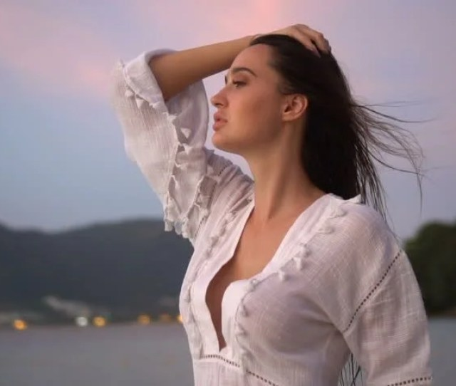 Closeup Portrait Of Sensual Woman In White Linen Dress Posing On The Sandy Beach On Tropical Paradise Island With Beautiful Summer Sunset Sky Video In