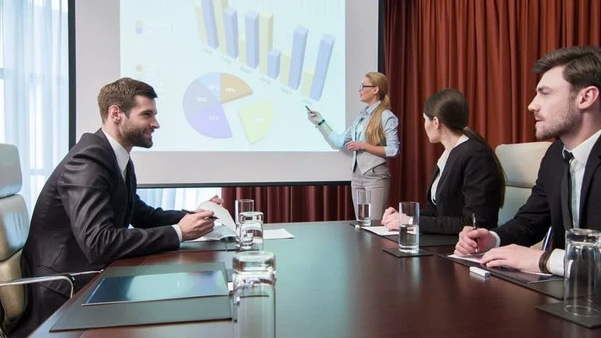 Business Meeting Group Of Young Business People Sitting In The Conference Room Against The